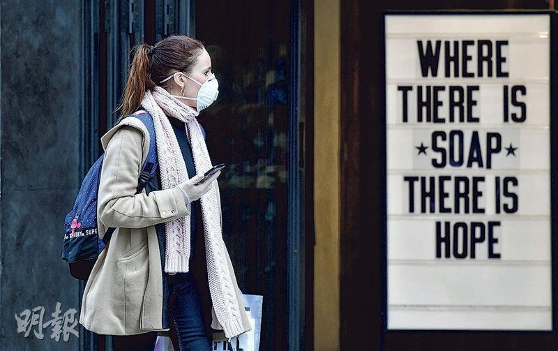 英國倫敦周五有戴口罩的路人走過一間寫有「只要有肥皂就有希望」的店舖。(路透社)