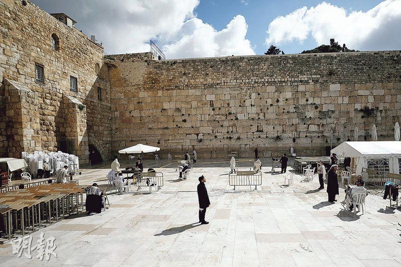 以色列周五起實施抗疫緊急措施,限制民眾非必要不能外出,耶路撒冷哭牆昨只有極少數禱告者。(路透社)