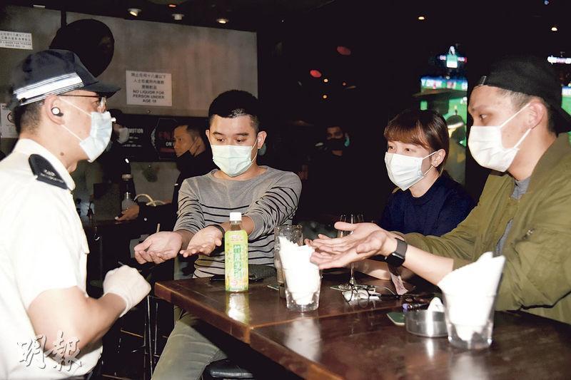 警方聯同醫療輔助隊人員昨晚到中環蘭桂坊,巡查會否有人違反隔離令外出,部分酒吧顧客向警員展示手腕,以示沒戴檢疫用的電子手環。(林智傑攝)