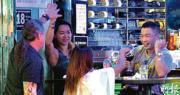 政府昨日宣布控疫新措施,特首林鄭月娥稱「飲醉少少會有更親密行為」,將制訂法例暫時禁止酒吧、食肆賣酒,但未有實行時間,稱會分秒必爭。昨晚灣仔駱克道一帶仍有人在酒吧聚集,除下口罩喝酒消遣。(林靄怡攝)