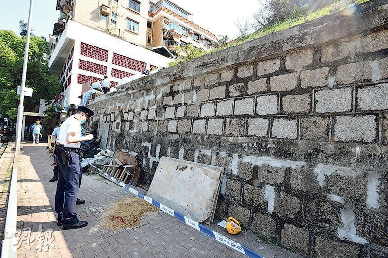 又一村學校斜坡正做維修工程,一名男工人昨早從約3米高的石牆頂墮下行人路,頭部重創,送院不治。警方事後在場調查。(衛永康攝)