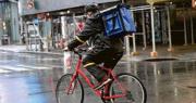 紐約市昨有外賣速遞員冒雨送餐。(法新社)