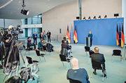 德國總理默克爾(中)周日在柏林就疫情舉行記者會,她跟在場記者都保持社交距離。(路透社)
