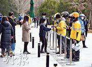 新冠肺炎疫情期間,北京復工企業的員工不少選擇外賣訂餐。圖為3月12日,午膳時間的北京望京SOHO寫字樓外,有外賣送餐員在此等候訂餐者前來取餐。(中新社)