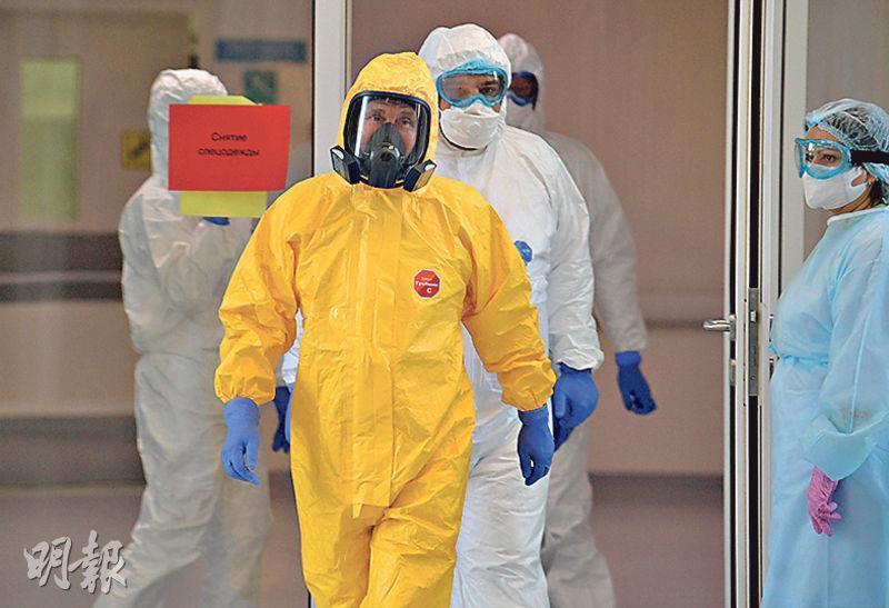 俄羅斯總統普京(前)昨日身穿防護裝備,到莫斯科市郊一間接收新冠肺炎患者的醫院視察。(路透社)