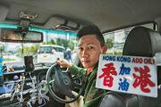 的士司機阿Jim在車廂內掛上「香港加油」的牌,車內又常備口罩,隨時送給有需要的乘客。他說,「幫到人梗係開心啦,香港人幫番香港人。」(林靄怡攝)