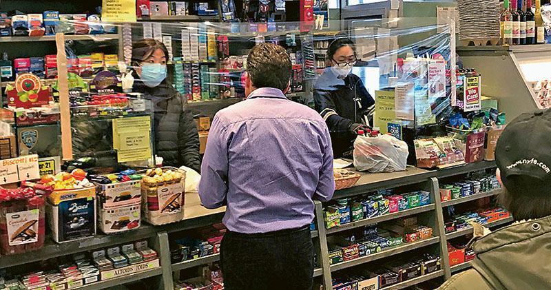 在紐約曼哈頓一家商店,周三有店員在櫃台透明膠屏障後為顧客服務。(路透社)