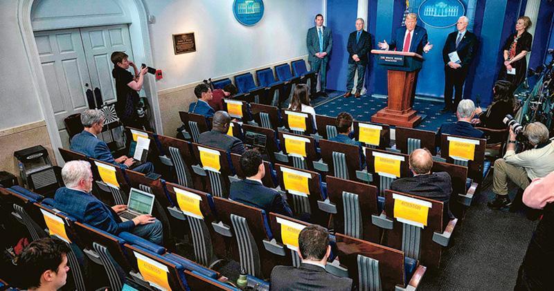 特朗普當地時間周四(26日)在白宮舉行新型冠狀病毒每日簡報會,質疑中國的確診數字,又提及當晚將與習近平通話。現場可見記者雖無戴口罩,但座位都保持距離。(法新社)