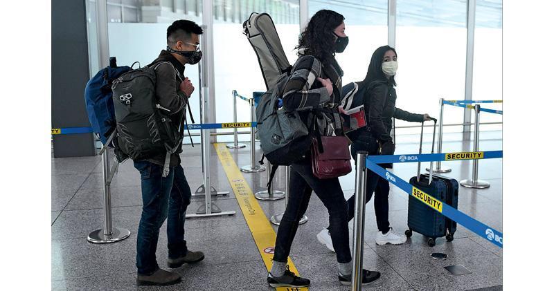 《華爾街日報》記者Stu Woo(左),Julie Wernau(中)和Stephanie Yang(右)於28日進入北京首都機場安檢區。中國18日宣布驅逐該報記者,他們被迫離開。(法新社)