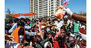 印度實施全國封城後,新德里市郊昨日有大批移民工人及其家屬,在高速公路等巴士返回自己的村落,其間有警員向他們派發麵包。(路透社)