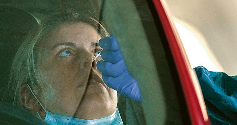 上周六在西班牙布爾戈斯市的一間大學醫院,全身防護裝束的衛生保健人員向一名司機抽取檢測新冠病毒樣本。(法新社)