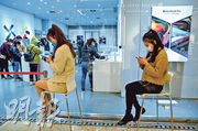 圖為昨武漢武商廣場一家復工手機店外,顧客等候進店。(中新社)