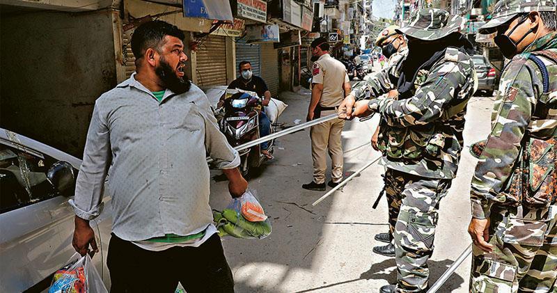 印度上周二起全國封城21天,在印度新德里,周三有警察揮棍打一名違反封城令的居民。(路透社)