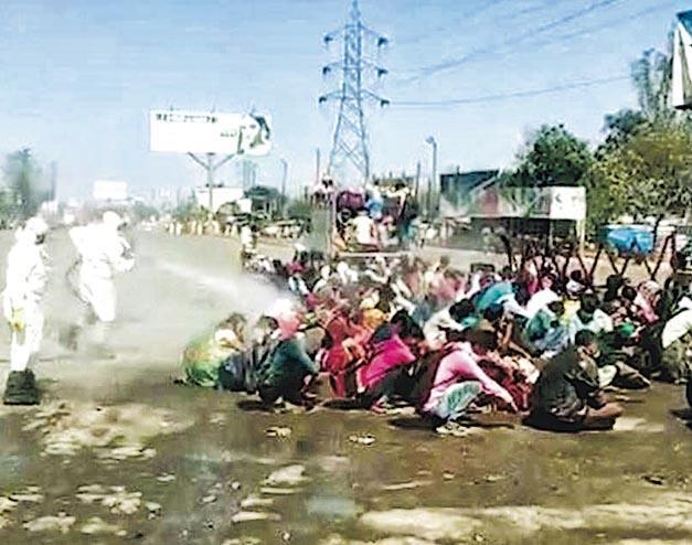 網上片段顯示印度北方邦巴雷利全副裝備的防疫人員,向一批蹲坐於空地的民工噴消毒劑。(網上圖片)
