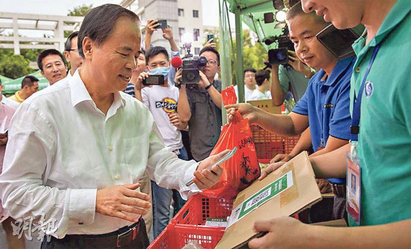 海南書記陳賜貴(左)前日率領官員到市集購物,照片所見他並無戴口罩。(網上圖片)