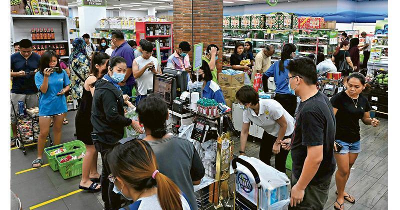 新加坡總理李顯龍公布更嚴厲抗疫措施後,超市出現搶購的顧客。(法新社)