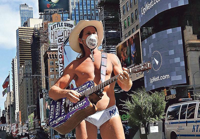 封城令下,紐約周四仍有街頭藝人戴上牛仔帽和口罩赤裸上身表演。(法新社)