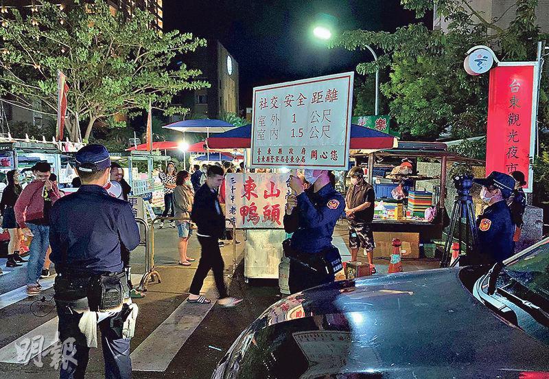 清明假期,台東觀光者眾,有警員昨在夜市用展板和大聲公宣傳防疫。(中央社)