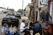美國新奧爾良是較多黑人居住的城市之一,當地有民眾周二在街頭玩撲克牌,其間有玩家除下口罩喝啤酒。(路透社)