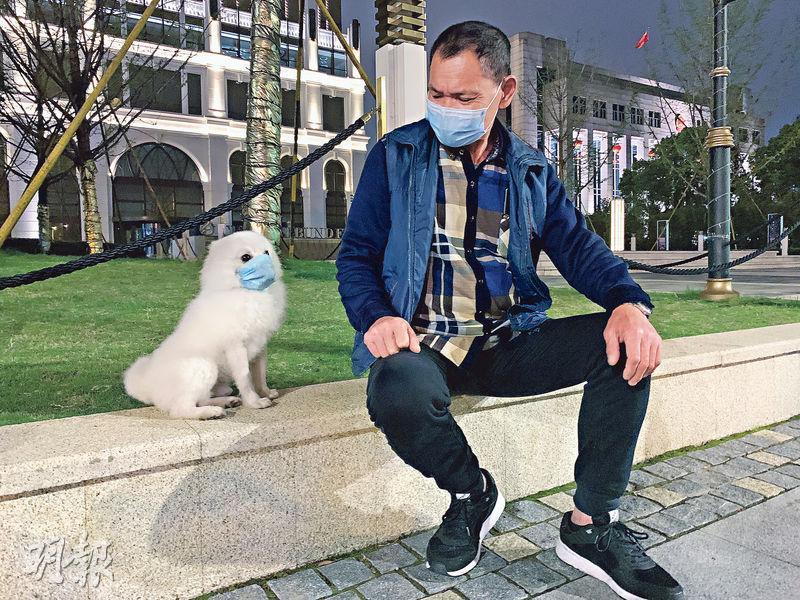 農業農村部周三發布《國家畜禽遺傳資源目錄(徵求意見稿)》,其中狗被指已「特化」為伴侶動物,不宜列入畜禽管理。圖為日前武漢市江岸區沿江大道,一名武漢市民與他戴口罩的小狗「妙妙」。(新華社)