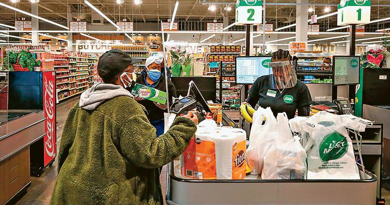 在芝加哥一間超市,周三有收銀員戴着防護面罩為顧客服務。(法新社)