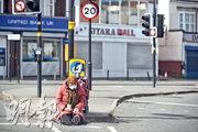 在英國伯明翰,一名露宿者周二戴着口罩和手套坐在街頭行乞。(路透社)
