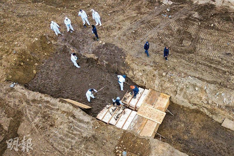 無人機周四拍攝的照片顯示,工人在紐約市赫特島公墓忙於埋葬多具棺木。(路透社)