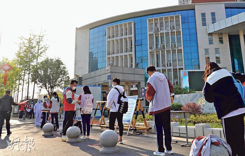 河南多地初三年級學生昨日迎來開學復課。圖為河南鄭州第四十八中門口,學生排隊返校復課。(中新社)