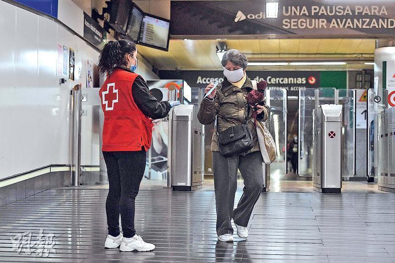 西班牙昨有紅十字會義工在馬德里的查馬丁車站派口罩。(法新社)