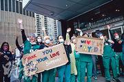 紐約市有醫務人員周日站在一家醫院外,手持寫有「感謝你們的愛心與支持」的致謝牌,回應消防員、警察、群眾給予的鼓勵掌聲。(路透社)
