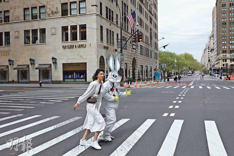 周日的紐約曼哈頓第五大道,有人穿了胸前貼了紅心的連頭套防護衣,戴上防護面罩和拿着一個賓尼兔頭像,以另類裝束慶祝復活節。(中新社)