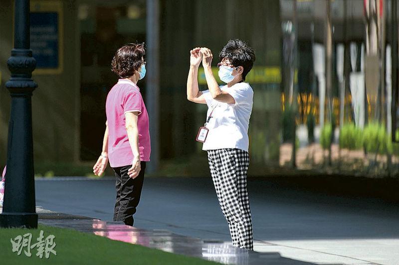 新加坡政府要求民眾出外必須戴口罩,否則初犯要罰款300坡元(約1640港元)。圖為昨日金融區內,有戴着口罩的婦女在舒展筋骨。(法新社)