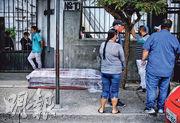 在厄瓜多爾的瓜亞基爾(Guayaquil),周日有民眾在墳場外等候,地上放有一具棺材。(路透社)
