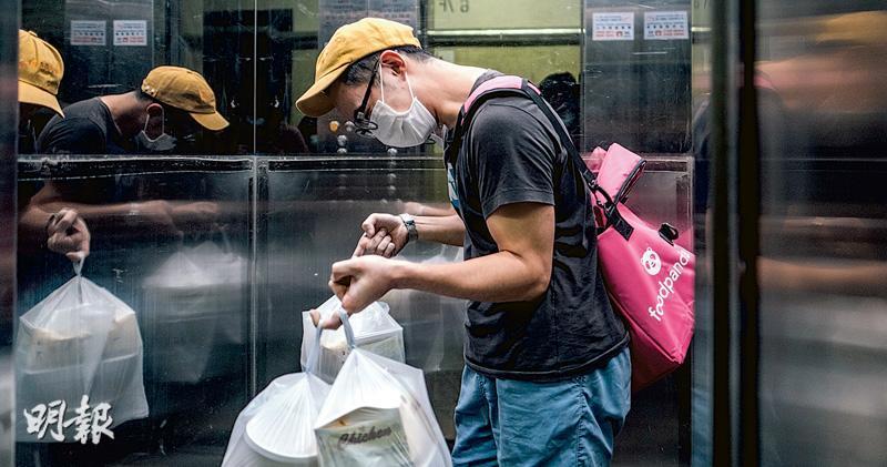 這晚子恒接到一宗700多元的韓國菜外賣單,由於外賣有湯,放進保溫袋容易打翻,他唯有雙手拿着三大袋食物,大嘆「真係重到懷疑人生,送咁重嘅嘢得30蚊」。(馮凱鍵攝)