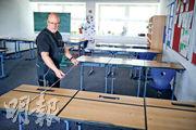 在德國城鎮小馬赫諾(Kleinmachnow),有學校職員昨準備課室,預備用於高中畢業考試。(路透社)