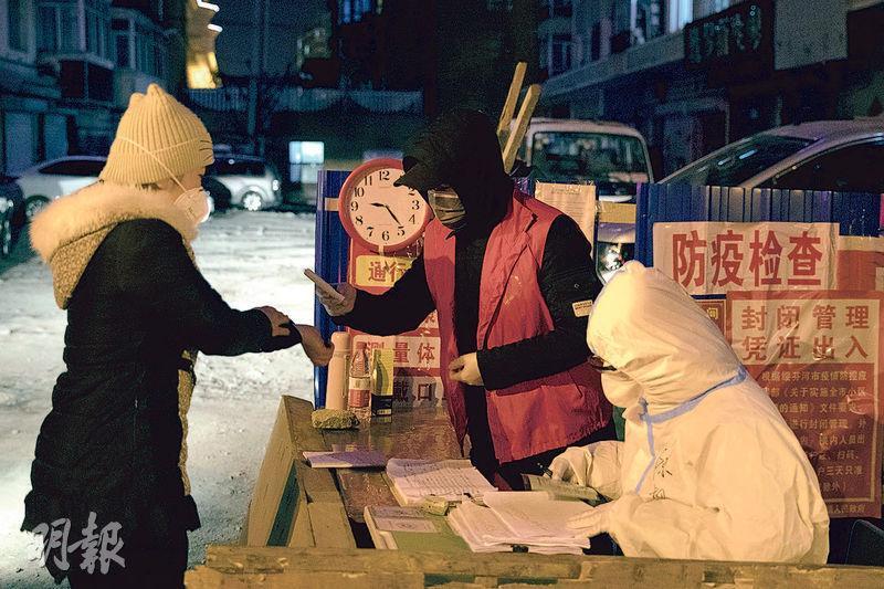 自多宗境外個案由黑龍江邊城綏芬河輸入後,當地加強檢疫。17日,在億正樓小區入口,工作人員為居民測體溫及辦理登記手續。(新華社)