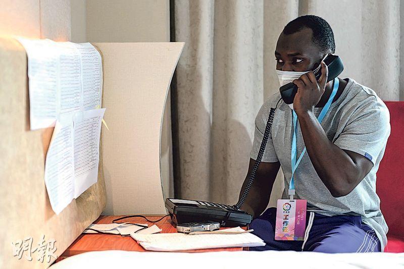 廣州早前有大批非裔人士感染個案,多人被隔離。圖為當地非裔志願者呂威廉昨日給在酒店隔離的外籍人員打電話,詢問他們的身體狀况。(中新社)