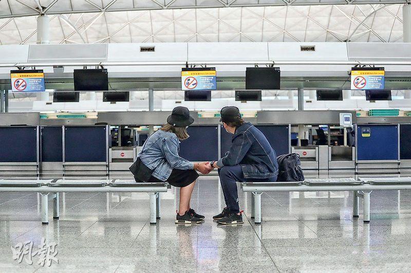 彭氏夫婦受訪這天重返機場,眼見離境大堂人迹罕至,「好似打咗一個月10號風球」,兩人嘆說現時生活是無止境等待,但仍期待疫情完結的一天,兩夫婦一起牽着手重返機場。(李紹昌攝)