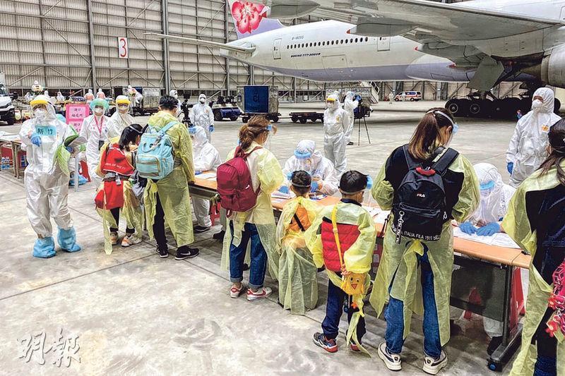 台灣航班接載滯鄂的台人返台後,在機棚內排隊接受消毒及檢疫。(中央社)