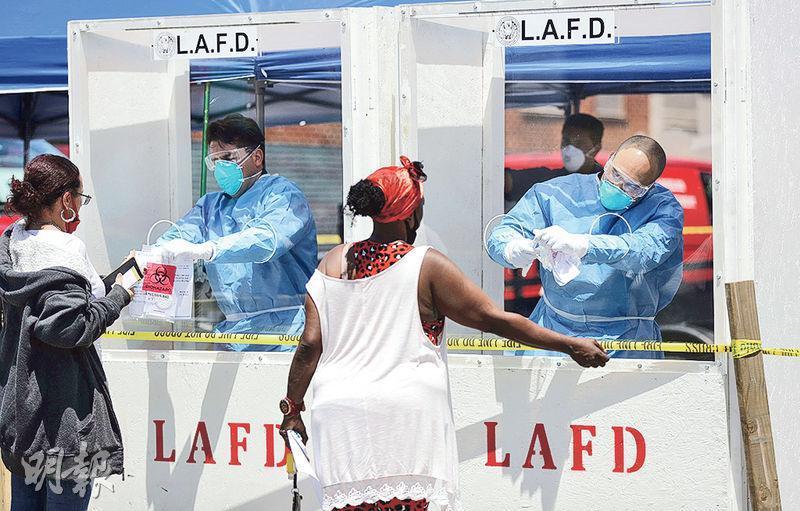 在洛杉磯,周二有消防人員在露宿者聚居地Skid Row為民眾收集樣本以檢測新冠病毒。當地一個露宿者庇護中心有43人確診。(法新社)