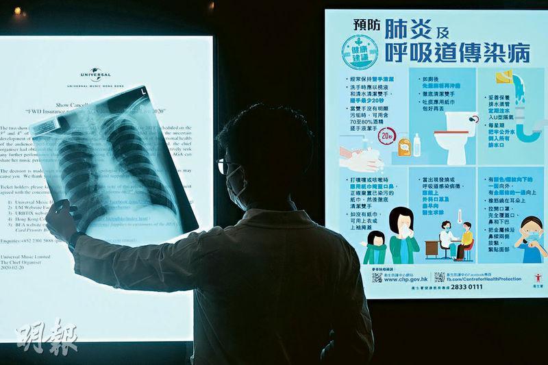 過去一個多月,放射師阿飛(化名)來回急症室與隔離病房,為新型肺炎疑似個案和確診者照肺部X光,雖近日確診數字回落,但阿飛說,到急症室檢測人流並沒有減少。圖中放射師手持的是本報其中一名記者的健康肺片。(馮凱鍵攝)