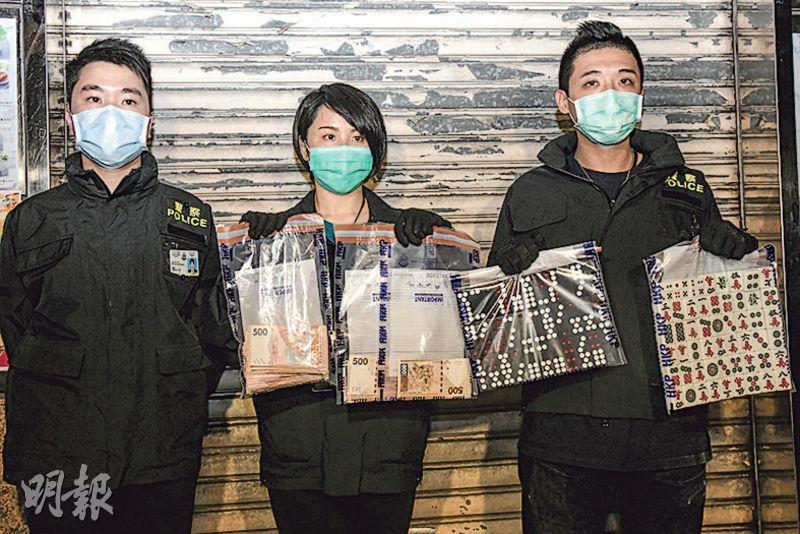 警方在深水埗青山道搗破非法賭檔,探員展示檢獲的賭具及賭款。(蔡方山攝)