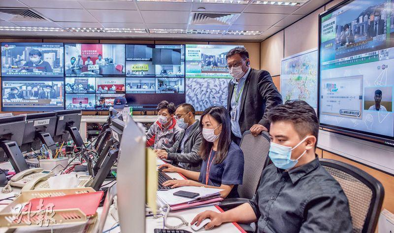 24小時有人當值的醫管局重大事故控制中心設電視直播新聞,也可同時與各聯網召開視像會議。每遇新型冠狀病毒確診高峰,重大事故控制中心的電話便響不停,中心聯絡人龔澤民(後)表示,有時同事正聽着兩個電話,枱頭另一個電話又響,全都是病人送院的要求。(鄧宗弘攝)