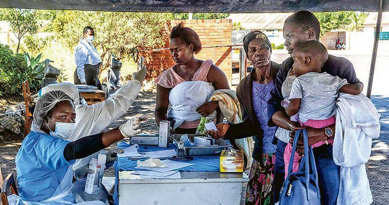 津巴布韋布拉瓦約一所醫院的醫務人員上周六為求診患者測量體溫。(法新社)