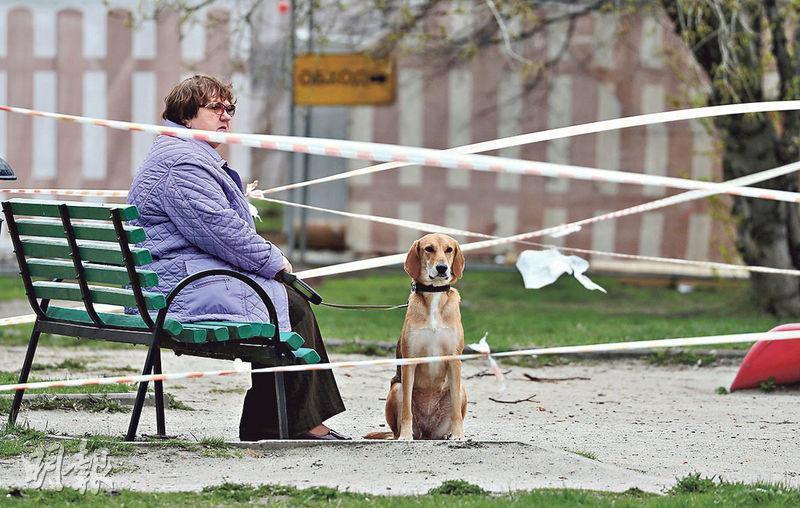 俄羅斯疫情嚴峻,不少地方仍封鎖禁止民眾聚集。圖為莫斯科一名婦人昨日拖着寵物犬在一個封鎖的兒童遊樂場內歇息。(路透社)