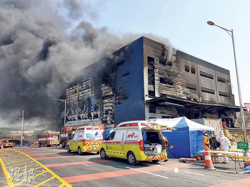 發生爆炸大火的韓國利川市物流倉庫地盤昨日嚴重熏黑和冒出黑煙,消防員及救護員在場戒備。(法新社)