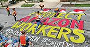 有示威者周三在亞馬遜創辦人貝索斯的美國寓所外畫上標語,敦促他要確保公司的工人得到防疫保護。(路透社)