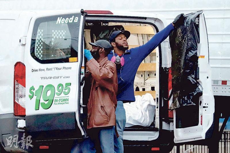 紐約市的「克萊克利殯儀館」以貨車暫存死者遺體,惹來民眾投訴。圖為工人周三在該殯儀館外整理裝屍的貨車。(路透社)