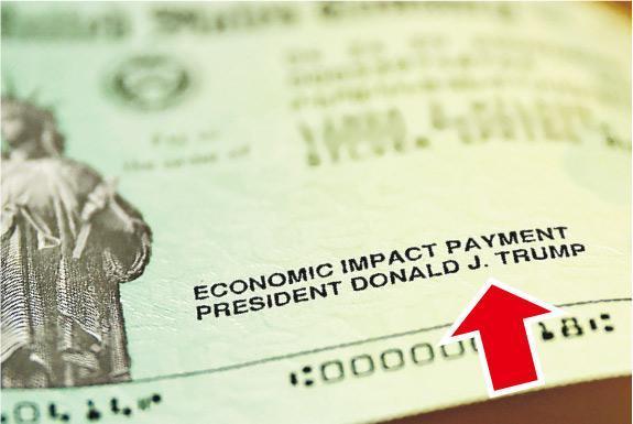 美國總統特朗普在疫情下爭取連任看來愈見艱難,其爭取曝光度的做法亦不斷惹爭議,例如是在救市支票留下他的名字(箭嘴示)。(法新社)