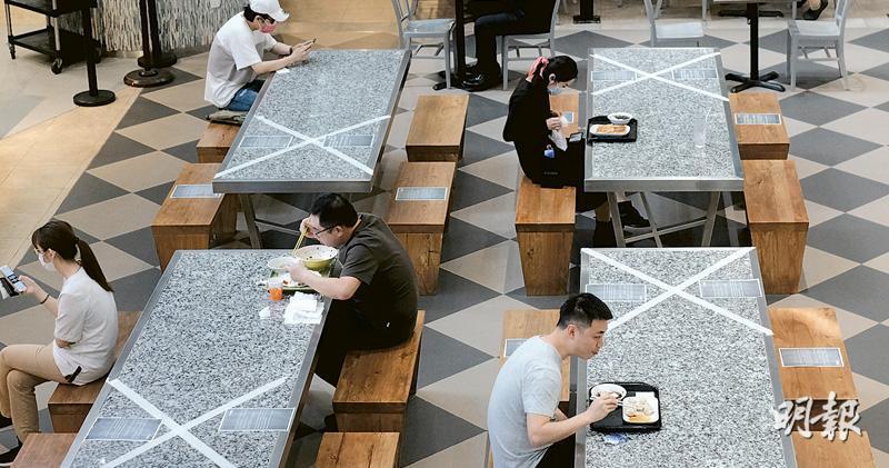 政府正檢視放寬食肆每枱最多坐4人的規定,圖為尖沙嘴的食肆在餐桌上貼上白色「交叉」標記,確保食客之間保持法例要求的距離。(賴俊傑攝)
